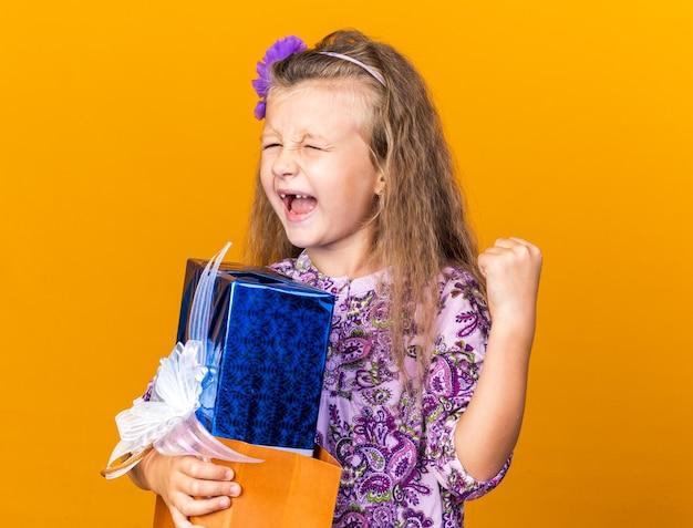 Eccitata bambina bionda che tiene in mano una confezione regalo e tiene il pugno alzato isolato sulla parete arancione con spazio per la copia