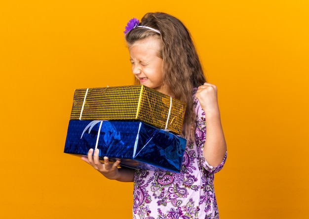 Excited little blonde girl holding gift boxes and keeping fist up isolated on orange wall with copy space