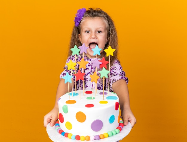 Excited little blonde girl holding and looking at birthday cake isolated on orange wall with copy space