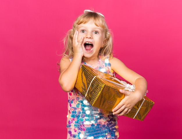 Excited little blonde girl putting hand on face and holding gift box isolated on pink wall with copy space