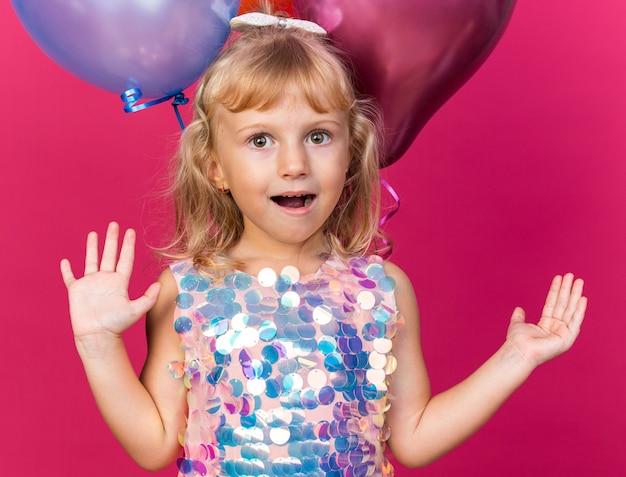 Eccitata bambina bionda in piedi con palloncini di elio alzando le mani in alto isolata sulla parete rosa con spazio di copia