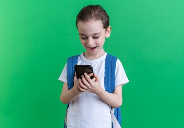 Eccitato ragazzino che indossa uno zaino che tiene e guarda il telefono cellulare isolato sulla parete verde con spazio di copia
