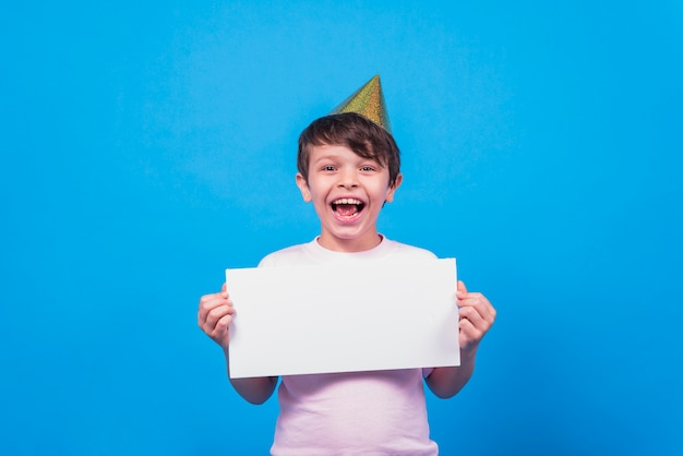 Excited little boy wearing party hat holding blank card in hand on blue surface
