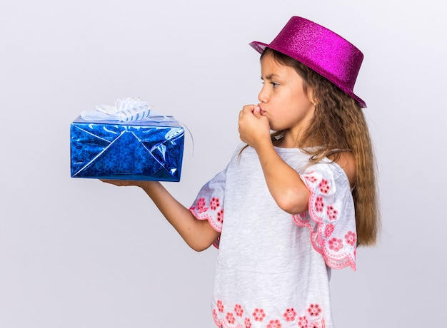 Excited little caucasian girl with purple party hat holding gift box and kissing fingers isolated on white wall with copy space