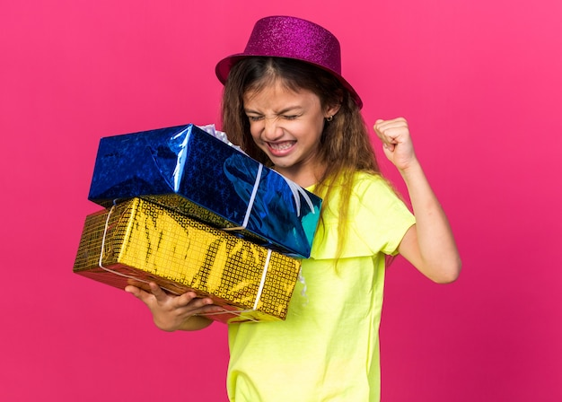 Excited little caucasian girl with purple party hat standing with closed eyes keeping fist up and holding gift boxes isolated on pink wall with copy space