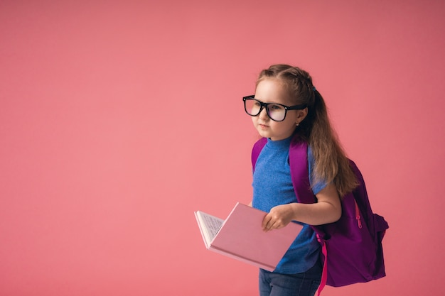 Excited little girl in glasses with school bag and holding book goes to school