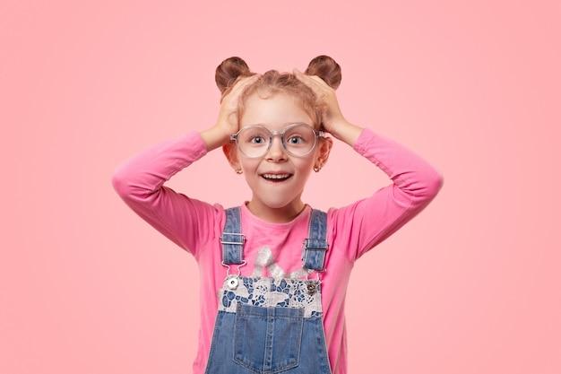 Возбужденная маленькая девочка в повседневной розовой рубашке и джинсовом комбинезоне и очках держит руки за голову и смотрит с шокированной гримасой