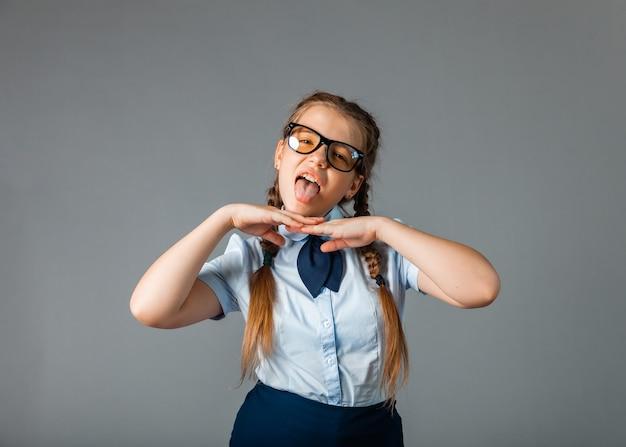 制服を着た興奮した少女と、灰色の背景に立って楽しんで10本の指を見せてくれるメガネ