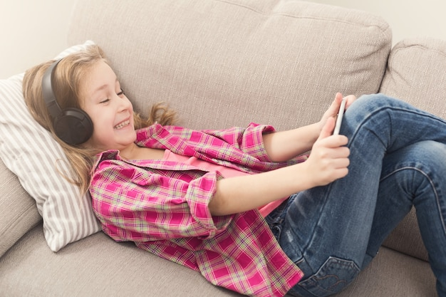 흥분된 어린 소녀는 스마트폰으로 온라인 게임을 하고 헤드폰으로 음악을 듣고 집에서 소파에 누워 있습니다. 현대 기술 중독 및 소셜 네트워킹 개념, 복사 공간