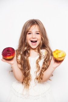 Excited little girl posing with donuts
