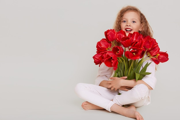 Excited little girl of school age sitting on floor with crossed legs and embracing bouquet of red tulips, having happy expression