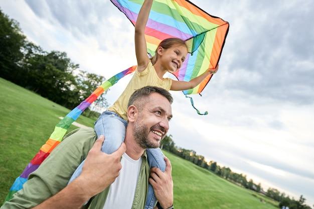 父親の肩に座って、美しい緑の色とりどりの凧を持って興奮した少女