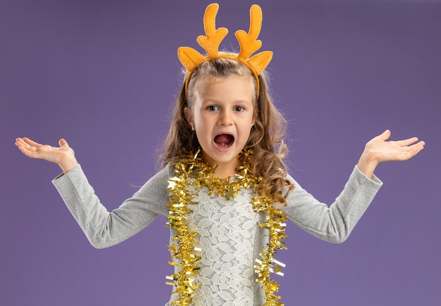 Excited little girl wearing christmas hair hoop with garland on neck spreading hands isolated on blue background