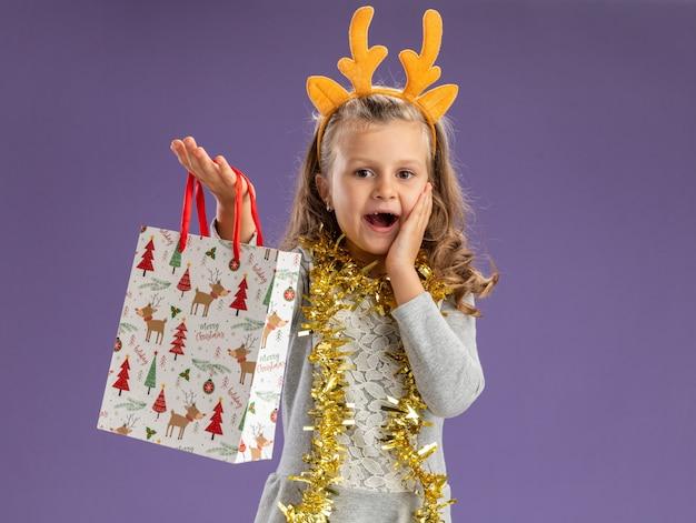 Взволнованная маленькая девочка в рождественском обруче для волос с гирляндой на шее, протягивая подарочный пакет перед камерой, положив руку на щеку, изолированную на синем фоне