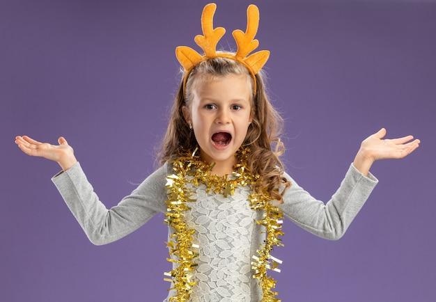 青い背景で隔離の手を広げて首に花輪とクリスマスの髪のフープを身に着けている興奮した少女
