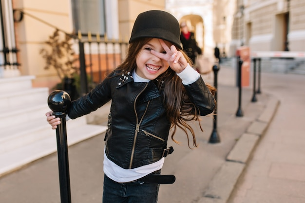 Excited little girl wearing leather jacket and belt holding iron pillar and posing with peace sign on city background.
