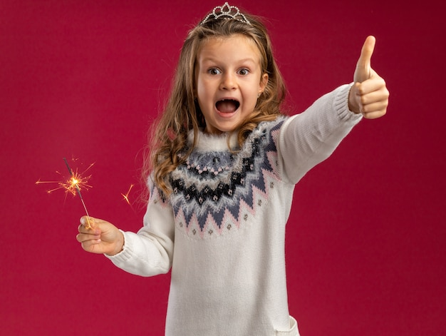 Excited little girl wearing tiara holding sparklers showing thumb up isolated on pink background