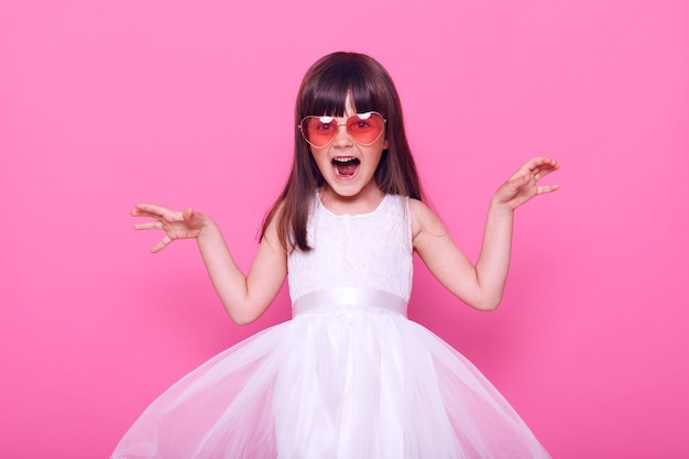 Excited little girl in white dress yelling with anger and frighten somebody, raising her hands, looking at front, having dark hair nd stylish glasses, isolated over pink wall
