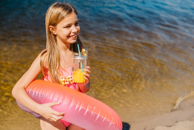 Excited little girl with bright swim ring on seashore
