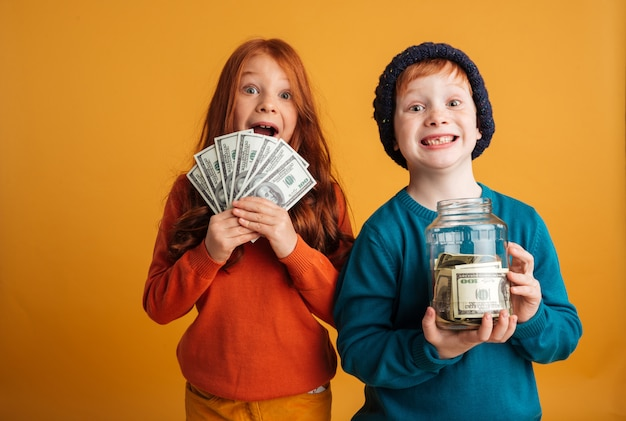 Excited little redhead children holding money.