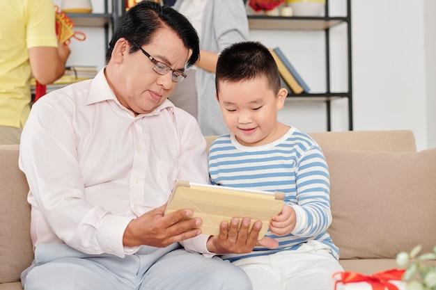 Взволнованный маленький вьетнамский мальчик и его дедушка смотрят мультфильм на планшетном компьютере
