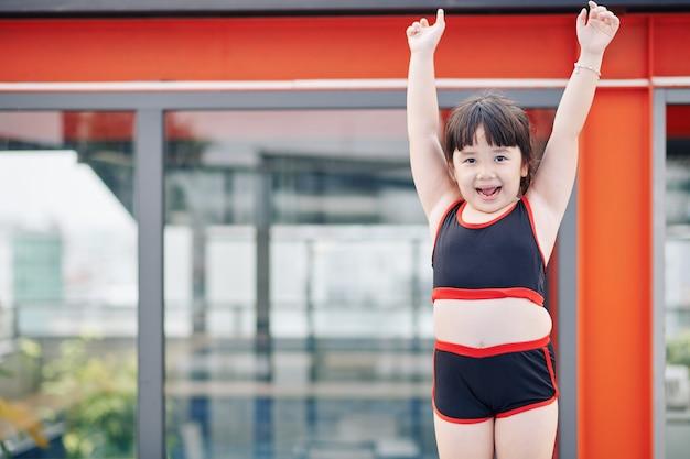 수영장에서 수영할 준비가 된 수영복을 입은 흥분한 베트남 소녀