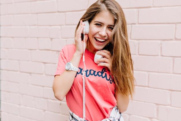好きな音楽を楽しみながら感情的にポーズをとる興奮した長髪の女の子