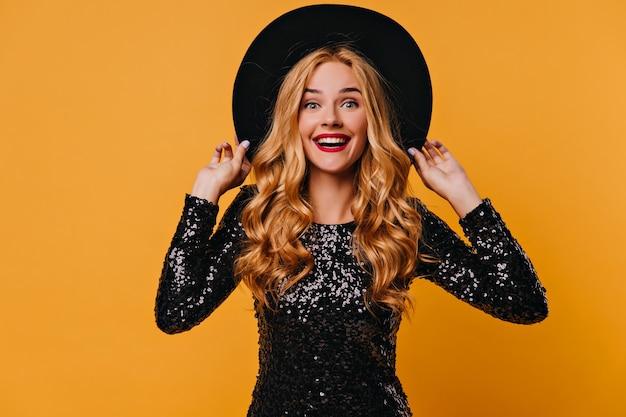 Eccitata giovane donna dai capelli lunghi che tocca il suo cappello nero. ritratto di ragazza stupita isolato sul muro giallo.
