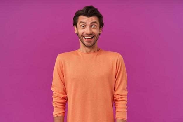 갈색 머리와 강모를 가진 흥분된 찾고 쾌활한 남자. 소매를 감은 오렌지색 스웨터를 입고