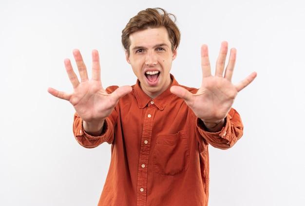 白い壁に隔離された正面に手を差し伸べる赤いシャツを着て興奮して見える正面の若いハンサムな男
