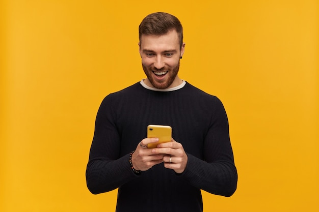 Excited looking male, handsome guy with brunette hair and beard. has piercing. wearing black sweater. holds smartphone and watching at it. reading a message. stand isolated over yellow wall