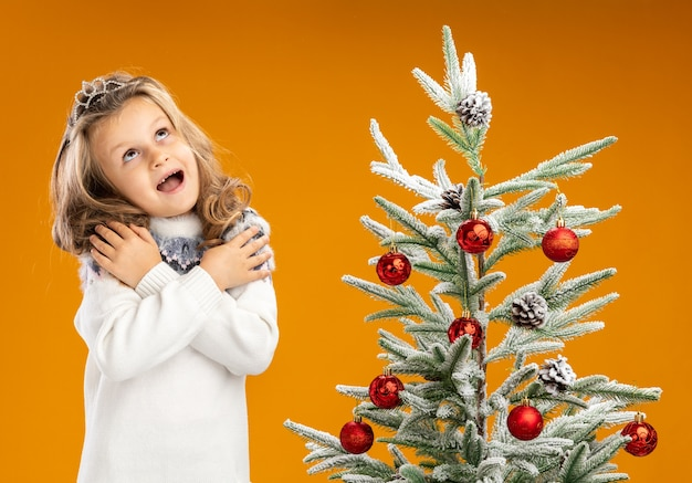 Excited looking up little girl standing nearby christmas tree wearing tiara with garland on neck putting hand on shoulders isolated on orange background