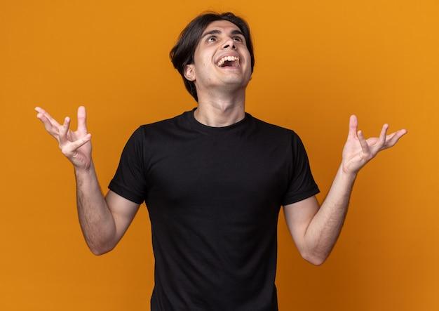 오렌지 벽에 고립 된 손을 확산 검은 티셔츠를 입고 젊은 잘 생긴 남자를 찾고 흥분