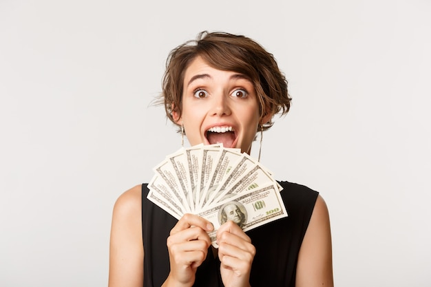 驚いてお金を持っている興奮した幸運な女の子