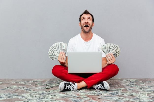 Взволнованный счастливчик держит банкноты и сидит на полу с ноутбуком на сером фоне