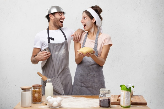 Excited male and female cooks rejoice their success, look at each other with smile, have overjoyed expressions