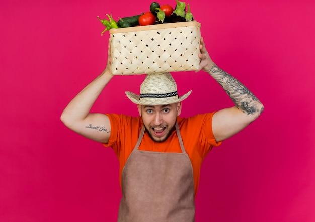 ガーデニング帽子をかぶって興奮している男性の庭師は頭上に野菜のバスケットを保持します