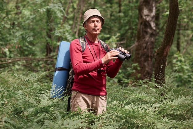 Excited male hitch hiker standing among trees with binoculars in forest, looks concentrated, elderly male wearing casual red sweater