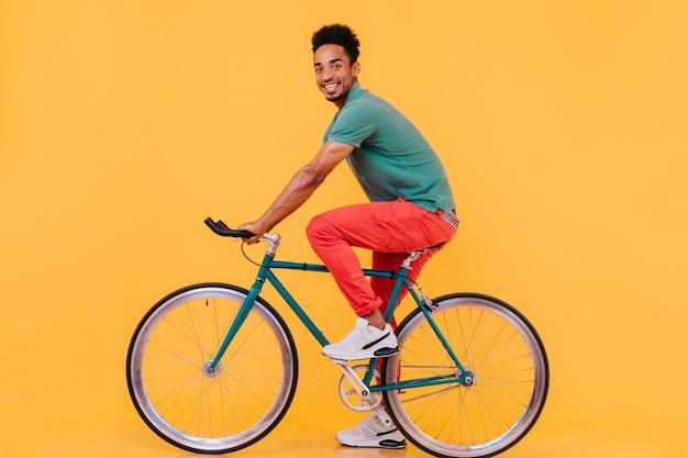 自転車でポーズをとるスポーツの白い靴で興奮した男性モデル。自転車に座って見ている陽気なアフリカ人の屋内写真。