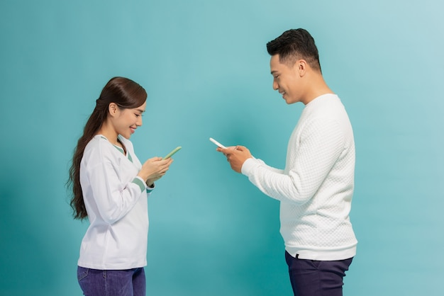 흥분된 남자와여자가 파란색 위에 서 서로보고 지주 스마트 폰 이야기.