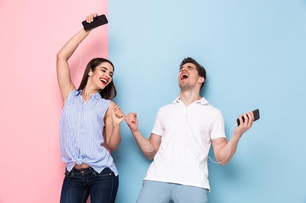 Возбужденные мужчина и женщина в наушниках слушают музыку на сотовых телефонах, изолированные на красочной стене