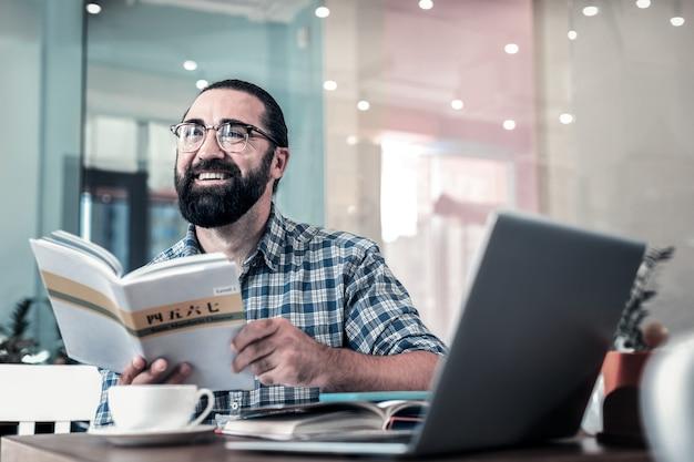興奮した男。外国語を勉強しながら興奮している元気なひげを生やした黒髪の男を輝かせる