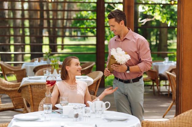 흥분된 남자. 여자 친구에게 멋진 흰색 꽃을 선물하면서 매우 흥분된 돌보는 잘 생긴 남자