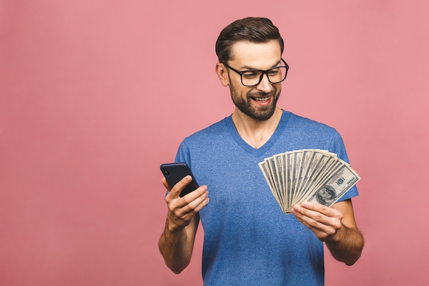 Excited man in casual t-shirt holding lots of money in dollar currencys and cell phone in hands isolated over pink wall.