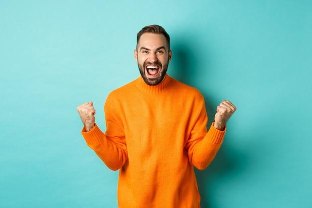 흥분된 남자는 승리를 축하하고, 기뻐하며 주먹 펌프 제스처를 만들고, 승리하고 만족스러워하며, 예, 목표를 달성하고 밝은 청록색 벽 위에 서 있습니다.