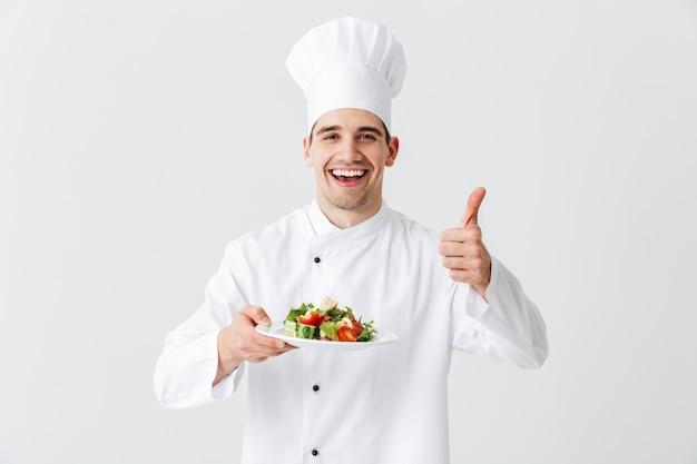 Взволнованный шеф-повар в униформе показывает свежий зеленый салат на тарелке, изолированной над белой стеной, показывает палец вверх