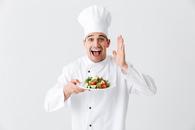 Взволнованный шеф-повар в униформе показывает свежий зеленый салат на тарелке, изолированной над белой стеной
