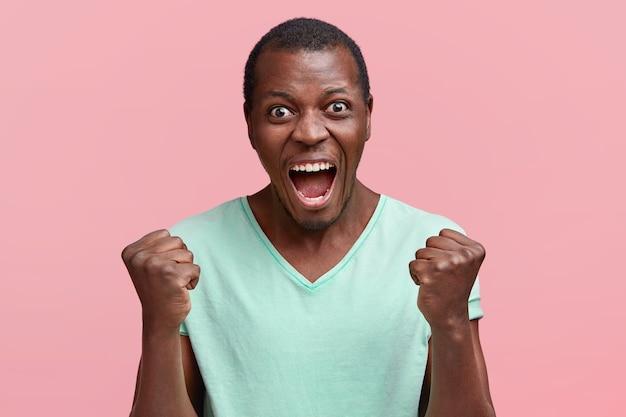 L'uomo eccitato stringe i pugni e urla ad alta voce, esprime la sua rabbia, vestito con una maglietta verde, sta contro il muro rosa