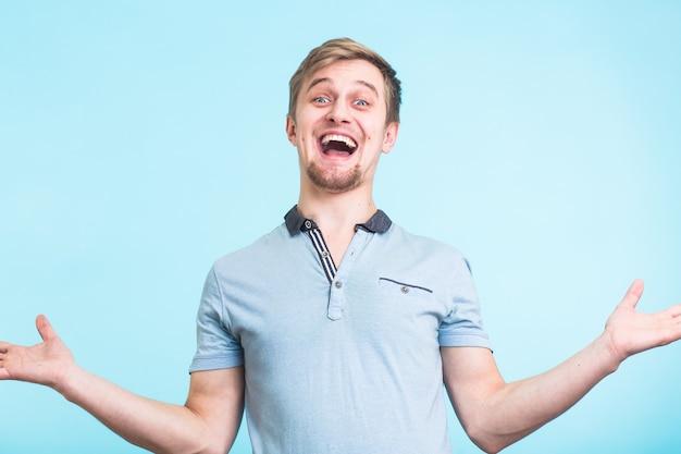 興奮した男は幸福で叫び、積極的に身振りで示し、大きな驚きを表明しました