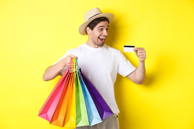 Excited man going shopping on vacation, looking satisfied at credit card, holding paper bags, standing over yellow wall